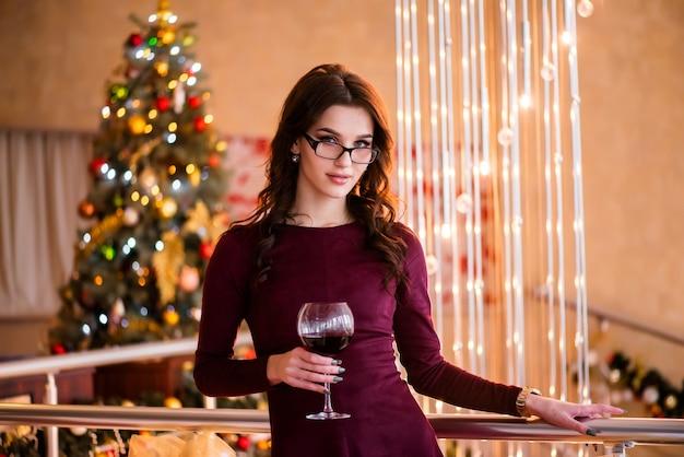 Красивая молодая женщина стоит с бокалом вина