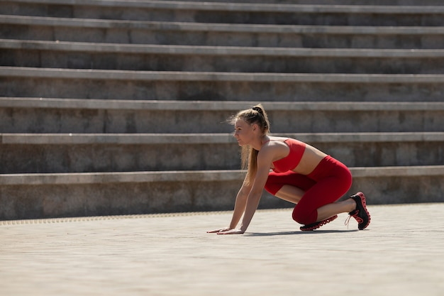 Beautiful young woman in start position in stadium in summer