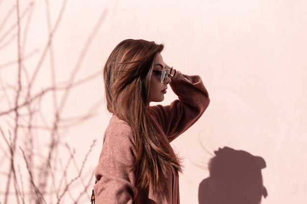Beautiful young woman straightens chic hair in city. attractive modern girl model in trendy sunglasses poses in vintage elegant coat near pink wall on sunny day outdoors. profile photo.