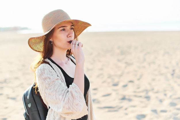 Beautiful young woman in straw hat on the beach