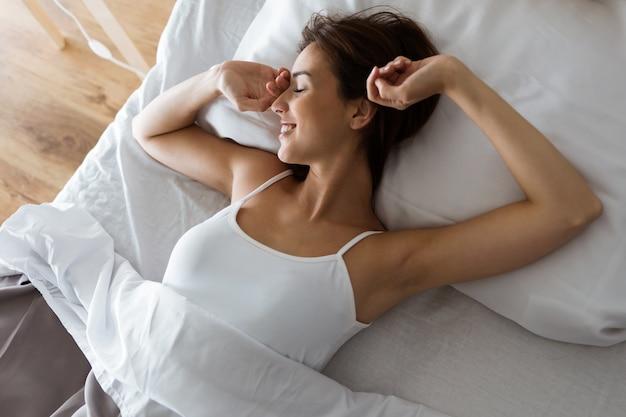 美しい若い女性は起床後にベッドでストレッチ。