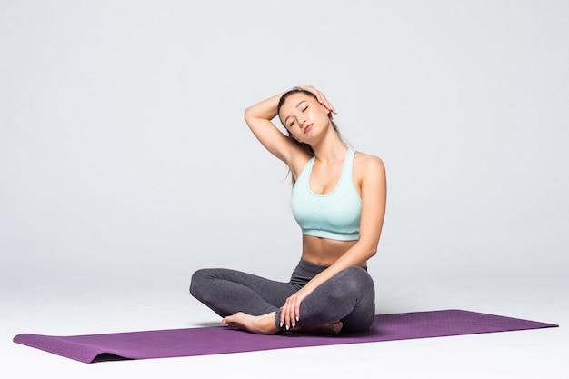 Bella giovane donna che allunga i muscoli delle braccia e della schiena isolati