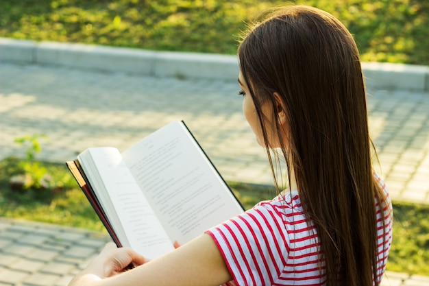 Beautiful young woman in striped t-shirt reading a book on the bench in the park.