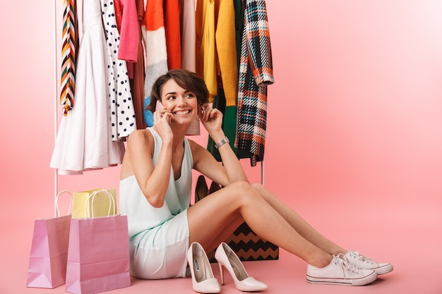 Beautiful young woman stylist sitting at the clothes rack, picking clothes, talking on mobile phone