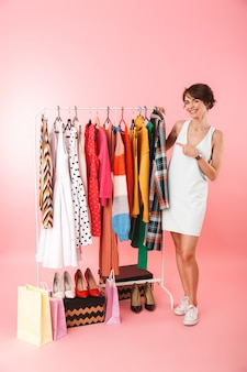 Красивая молодая женщина-стилист, стоя у вешалки для одежды, выбирая одежду