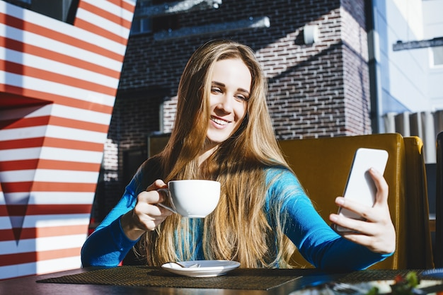 Beautiful young woman successful fashion and beautiful with a mobile phone and a cup of coffee in a cafe