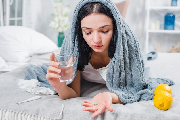 Beautiful young woman suffering from fever holding water glass and pills in hand