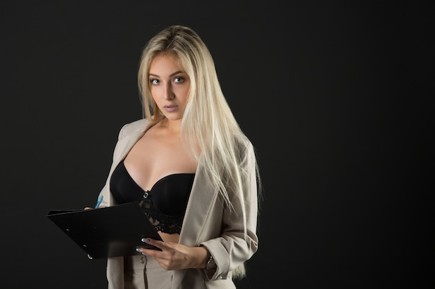 Beautiful young woman in a suit and sexy lingerie, with a folder and pen in hands