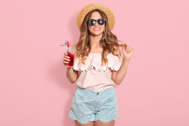 Beautiful young woman in summer blouse, blue short, black sunglasses and straw hat holding glass