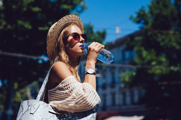 Bella giovane donna in occhiali da sole, bevendo un acqua dalla bottiglia, camminando all'aperto.