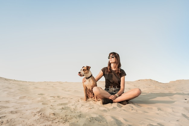 Beautiful young woman in sunglasses hugs with dog sitting on sandy beach or desert. girl in hiking casual clothes and staffordshire terrier puppy sitting in sand on hot summer day