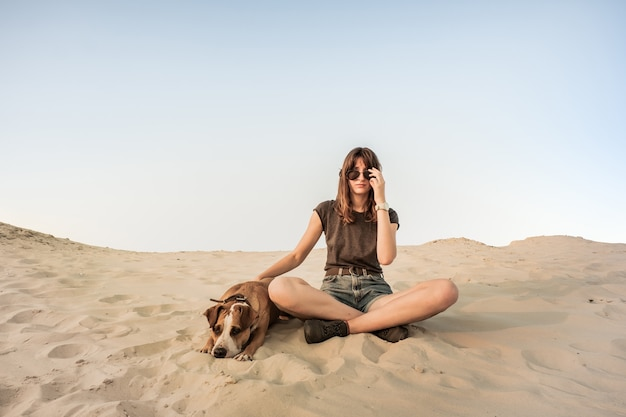Beautiful young woman in sunglasses rests with dog on sandy beach or desert. girl in hiking casual clothes and staffordshire terrier puppy sitting in sand on hot summer day