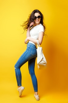 Beautiful young woman in sunglasses, white shirt, blue jeans posing with bag