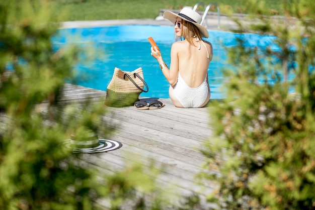 Beautiful young woman in sunhat relaxing near the swimming pool sitting back on the wooden poolside