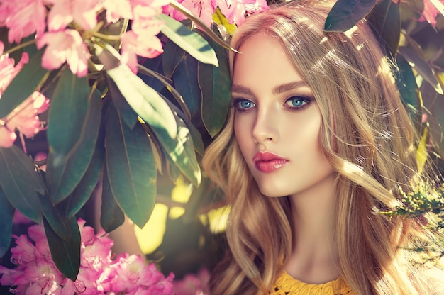 Beautiful young woman surrounded by blossoming flower trees. gentle makeup, rose lipstick and freely lying long hair curls.