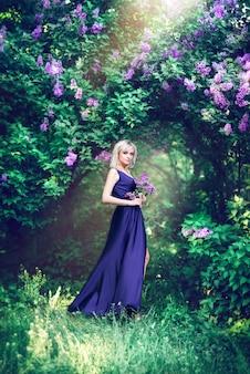 보라색 꽃으로 둘러싸인 아름 다운 젊은 여자. 라일락 봄 정원의 배경에 슬릿으로 긴 드레스에 여자. 화장품과 향수의 개념