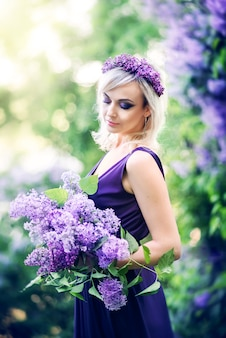 Beautiful young woman surrounded by purple flowers. woman is sitting in a long dress with a slit on the background of a spring garden with lilacs
