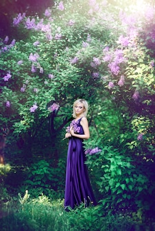 Beautiful young woman surrounded by purple flowers. woman in a long dress with a slit on the background of a spring garden with lilacs. concept of cosmetics and perfumes