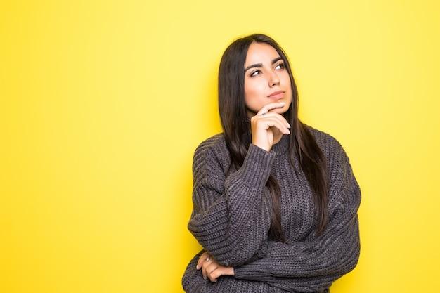 Красивый свитер молодой женщины улыбается и на желтом.