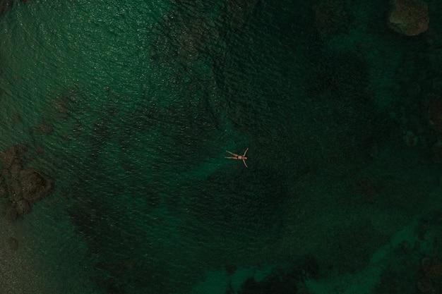 真ん中の海の水で一人で泳ぐ美しい若い女性。横になっている水着ビキニの女の子