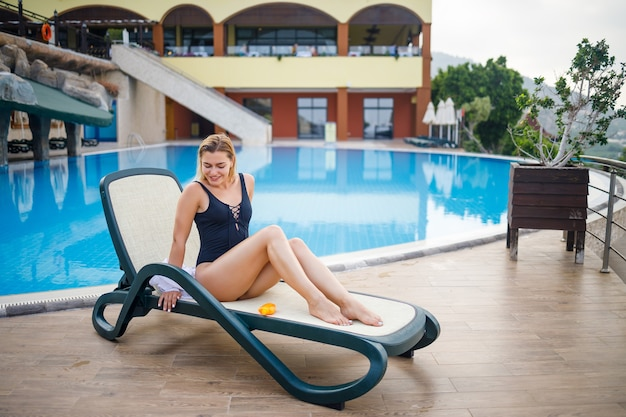 A beautiful young woman in a swimsuit and a white shirt sits on a sun lounger by the pool and rubs her body with sunscreen. summer skin care, protection against skin burning