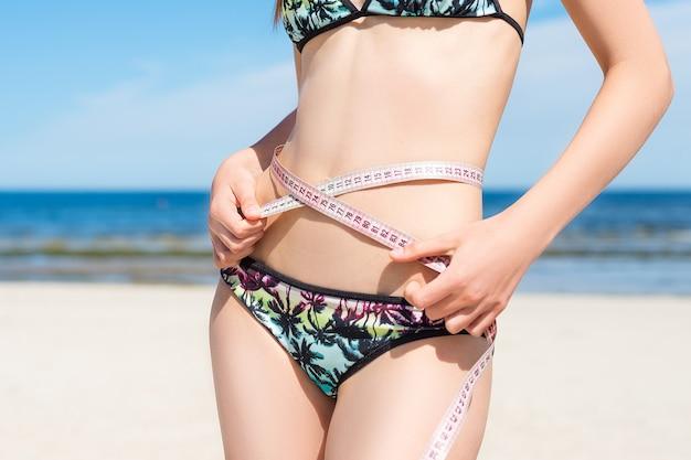 Beautiful young woman in swimwear measure perfect waist on sea background