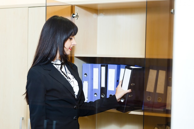 Beautiful young woman take a folder with documents from cabinet