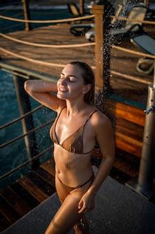美しい若い女性は、海沿いの屋外の晴れた日に水着でリラックスしたシャワーを浴びます。休暇中の女の子は休んでいます。セレクティブフォーカス