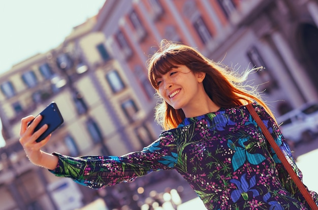Beautiful young woman takes a selfie in naples