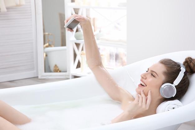 Красивая молодая женщина, принимающая ванну дома