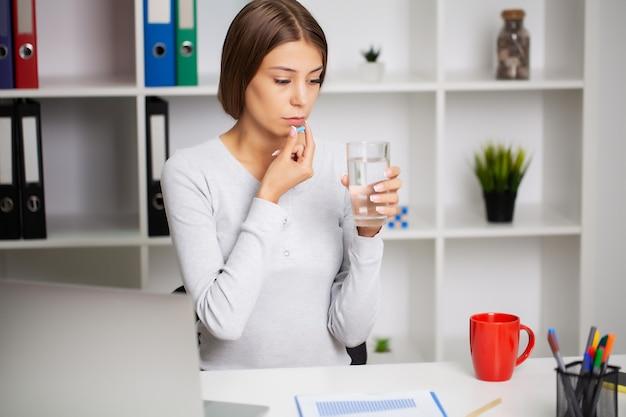 사무실에서 약을 복용하는 아름 다운 젊은 여자.