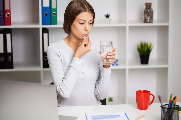 Beautiful young woman taking pill at office.