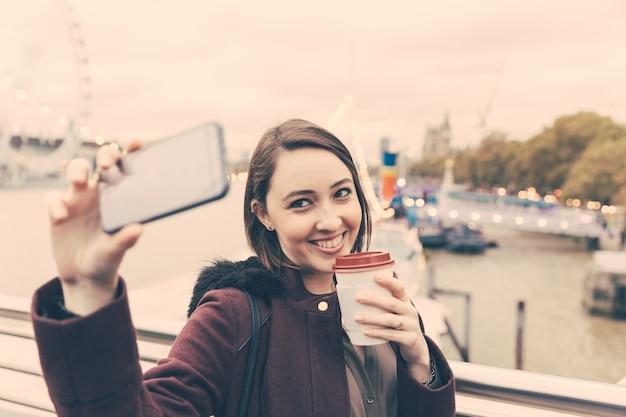 Beautiful young woman taking a selfie in london