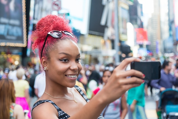 Beautiful young woman taking selfie in times square