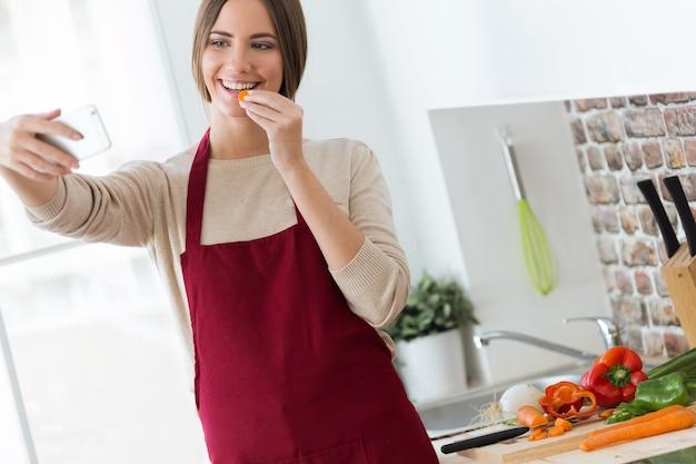 Bella giovane donna che cattura un selfie mentre si mangia le carote in cucina.
