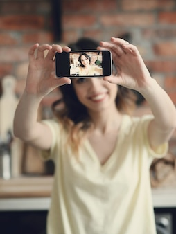 Beautiful young woman taking selfie with smartphone