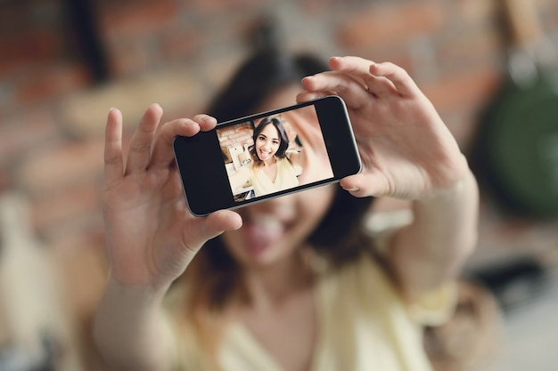 Красивая молодая женщина, делающая селфи со смартфоном