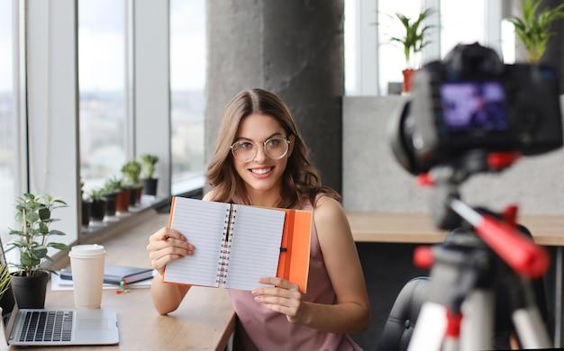 彼女のブログの新しいビデオを作成しながら話し、笑顔の美しい若い女性。