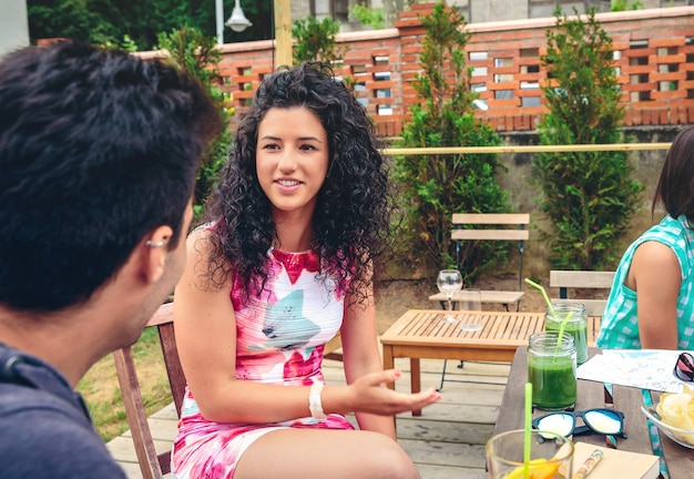 屋外での余暇の夏の日に健康的な飲み物とテーブルの周りの友人と話している美しい若い女性