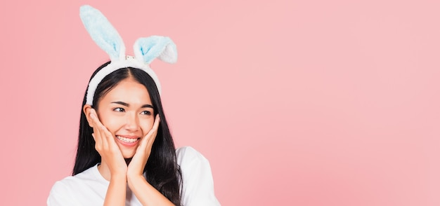 Beautiful young woman teen smiling wearing easter rabbit bunny ears holding her cheeks excited surprised