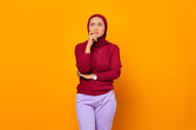 横を向いて新しいアイデアを発明する何かを考えている美しい若い女性