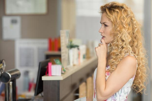 美しい若い女性は、カフェで何を買うべきかを考えています。中小企業、食品、人とサービスの概念
