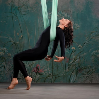 A beautiful young woman in a tight black tracksuit does yoga on a suspension