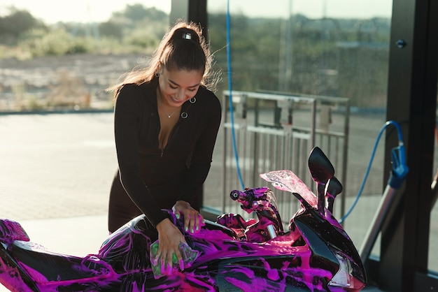 Beautiful young woman in tight-fitting black suit washes sport motorcycle and wipes it from magenta foam.