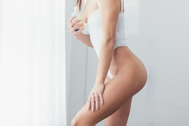 수화 크림과 로션으로 부드러운 아름다운 젊은 여성 터치 피부 다리