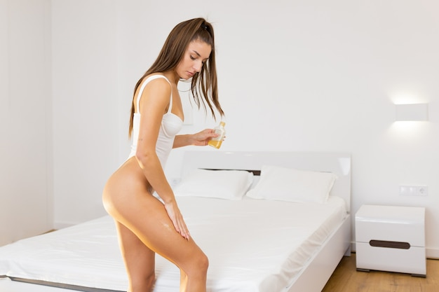 Beautiful young woman touch skin leg smooth with cream and lotion for hydration