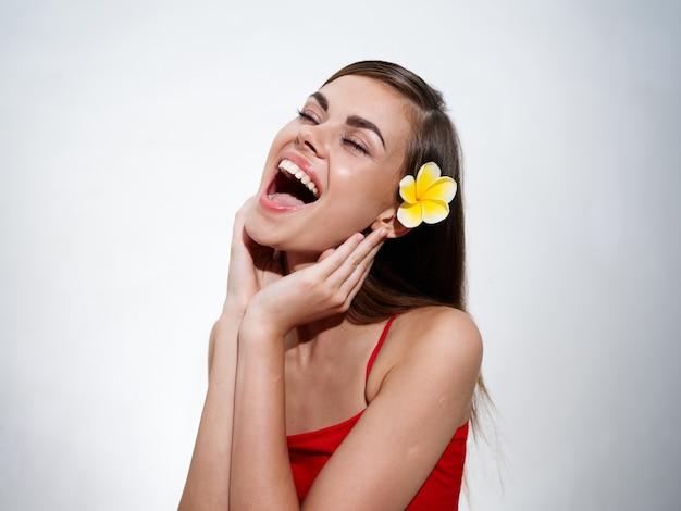 美しい若い女性は彼女の手で彼女の顔に触れ、彼女の口の広い黄色い花を開いた