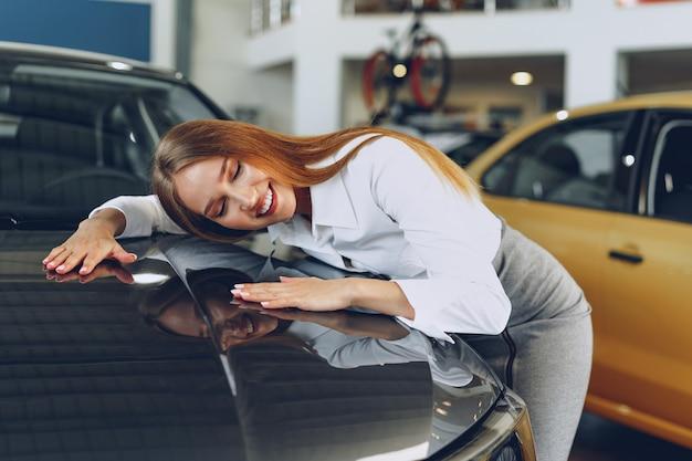 Красивая молодая женщина трогает свою новую машину с удовольствием и радостью