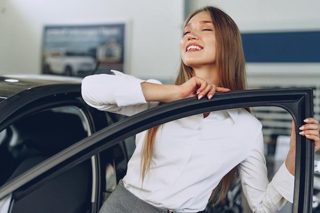 喜びと喜びで彼女の新しい車に触れる美しい若い女性