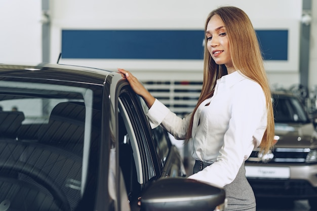 Beautiful young woman touching her new car with pleasure and joy